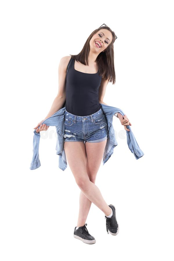 Happy young stylish woman in jeans shorts posing and smiling with denim jacket. stock image