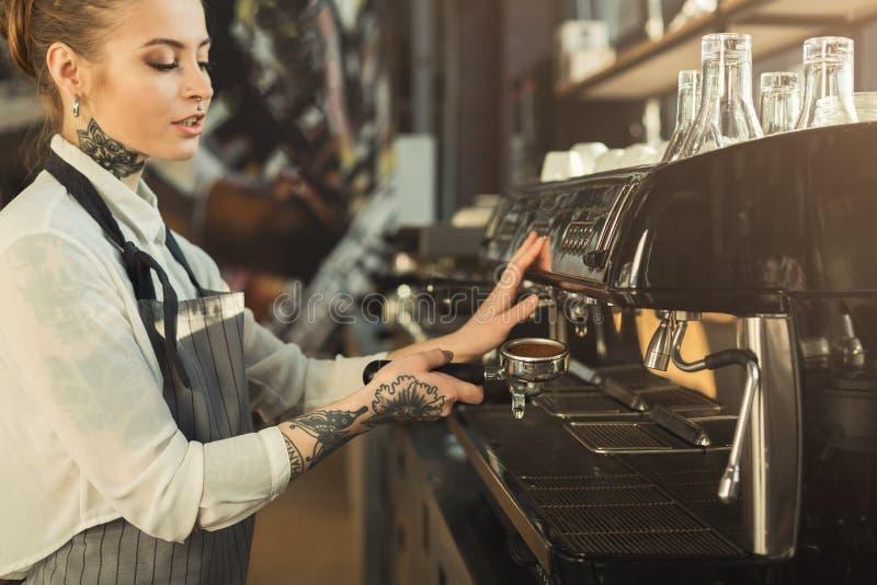 Tattooed barista making coffee in professional coffee machine stock photos