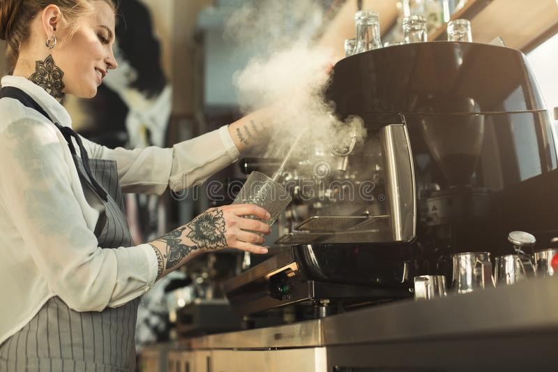 Tattooed barista making coffee in professional coffee machine stock photography