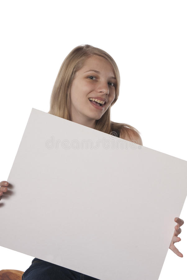 Happy young teenage girl holding blank sign. Young teenage girl holding blank sign in front of her. Ready for you text or advertisemant royalty free stock photo