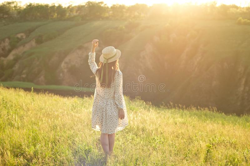 Happy young teenage student girl wearing a summer dress and straw hat in hands. Walking outdoors at the park. stock photo
