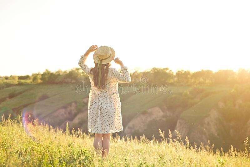 Happy young teenage student girl wearing a summer dress and straw hat in hands. Walking outdoors at the park. royalty free stock photography