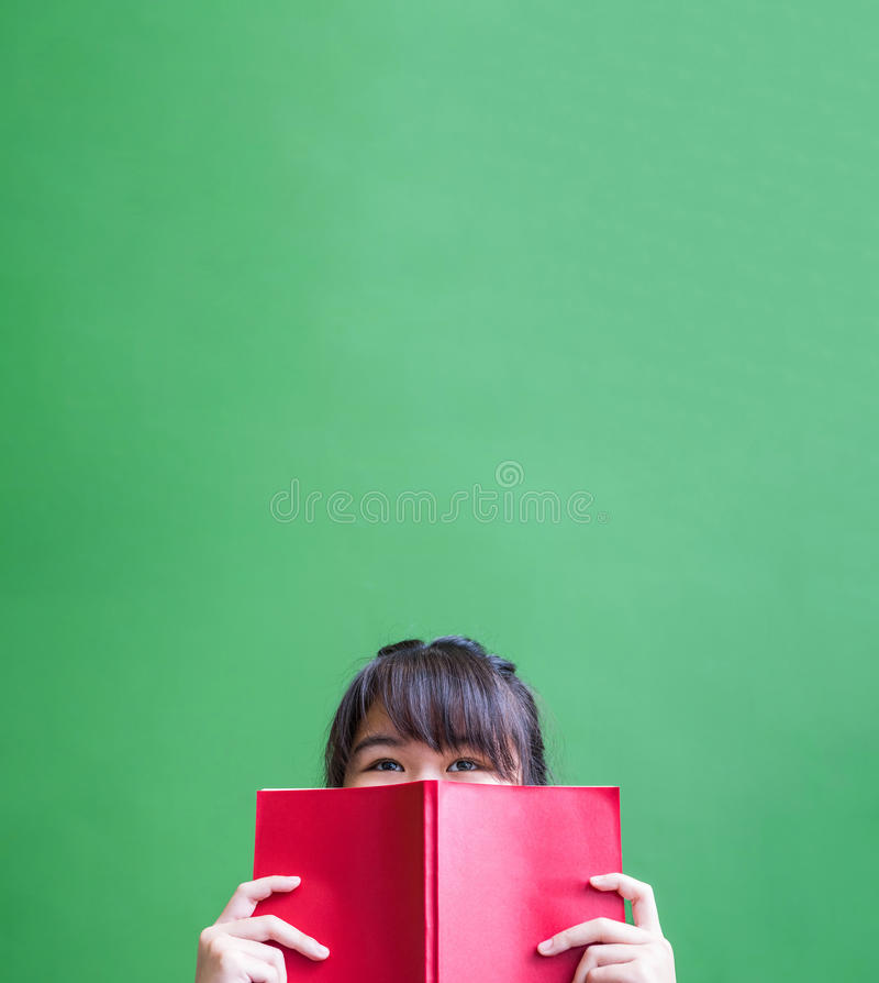 Happy young teenager girl holding red book cover face with think royalty free stock photo
