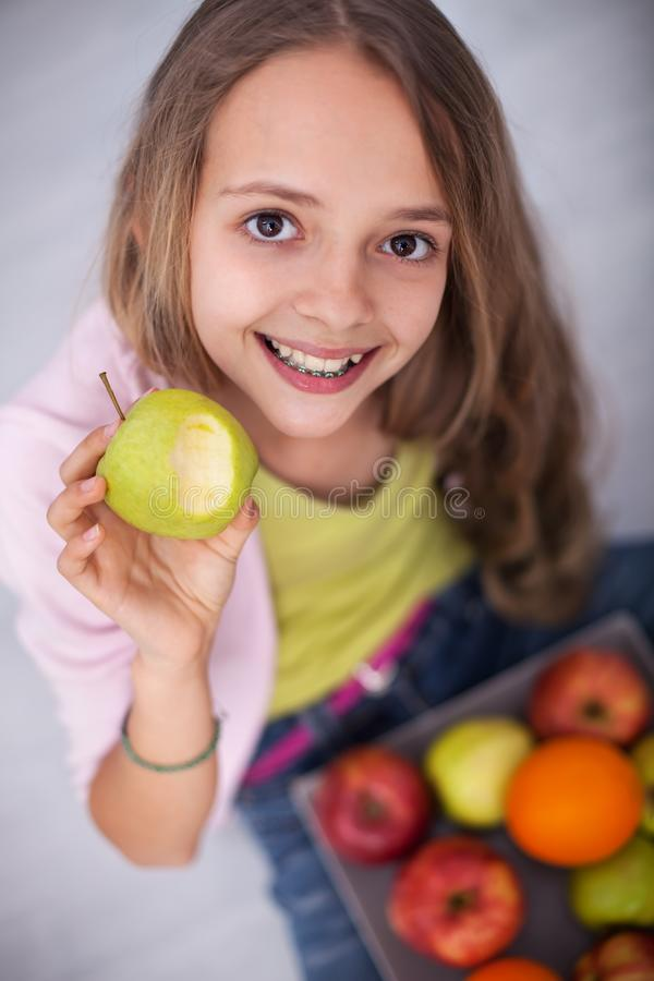 Happy young teenager girl sitting on the floor eating an apple royalty free stock images