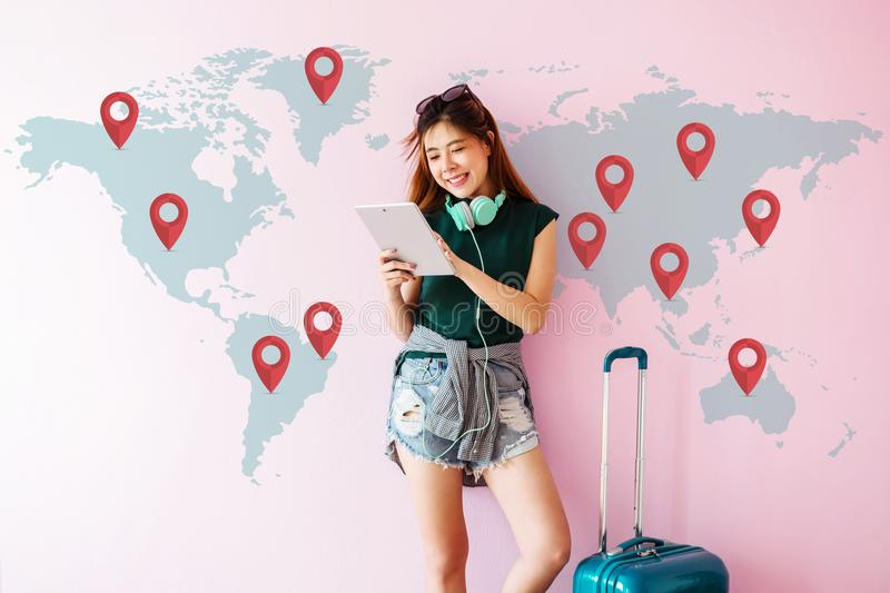 Happy Young Traveler Woman standing with Suitcase and using Tablet to Finding her Destination for Next Trip. Technology on Travel. Ing Concept. World Map with stock photography