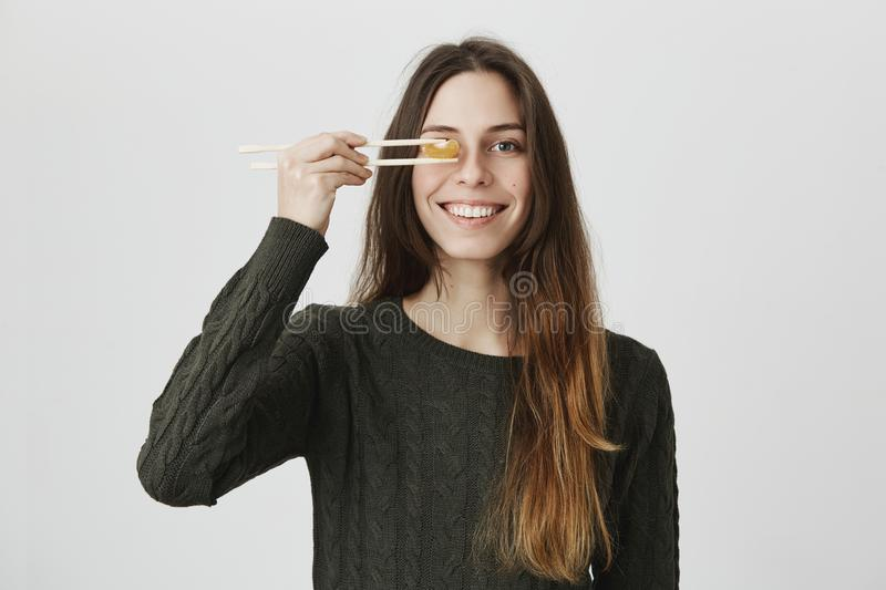 Happy young trendy female in green sweater smiles cheerfully to camera, covering eye with tangerine she holds using stock photography