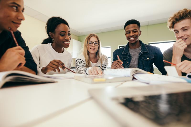 Group of multiracial people studying together. Happy young university students studying with books in college. Group of multiracial people in classroom royalty free stock photos