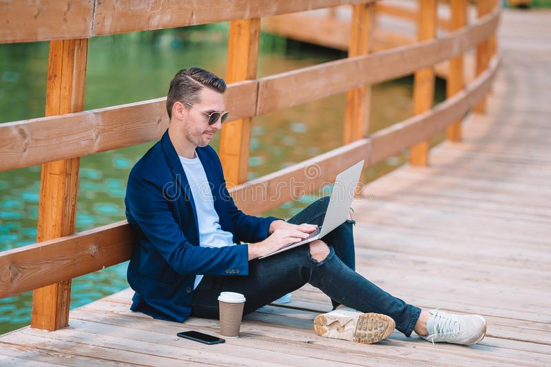 Happy young urban man working and drinking coffee in european city outdoors royalty free stock photo