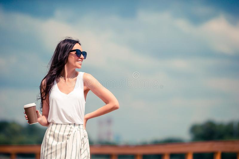 Happy young urban woman drinking coffee in european city. royalty free stock image