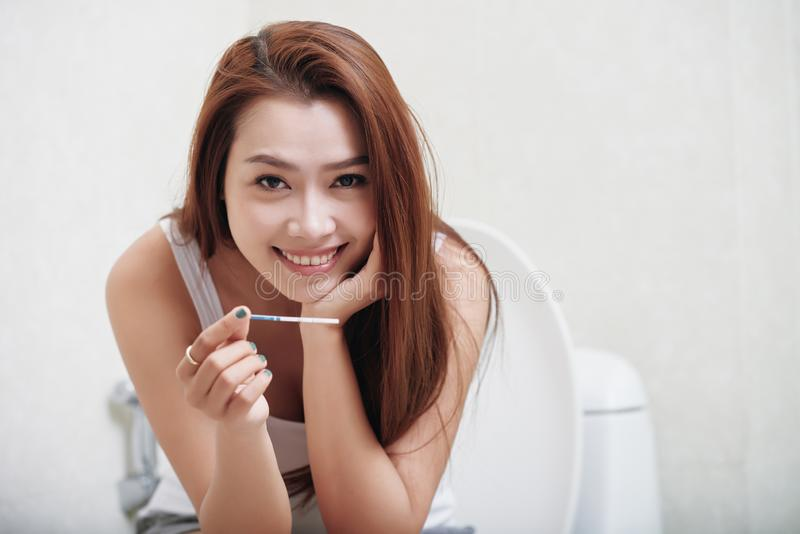 Pregnancy test. Happy young Vietnamese woman showing paper pregnancy test royalty free stock image