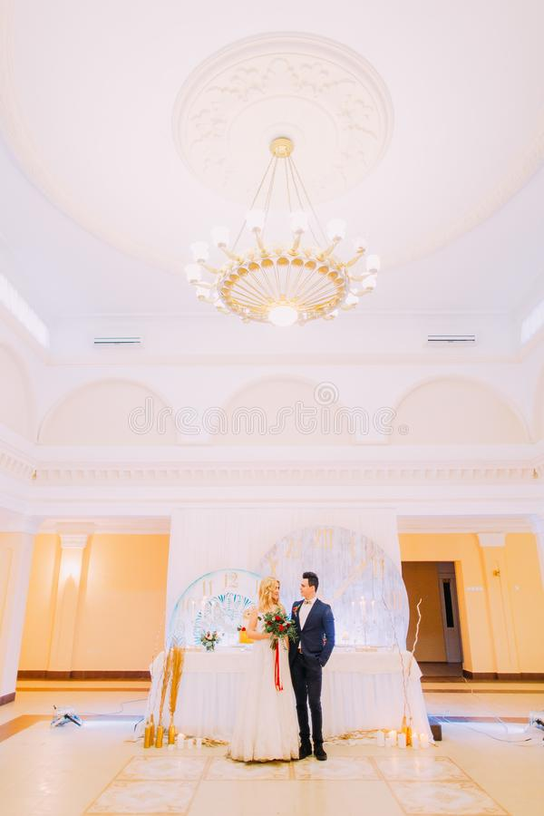 Happy young wedding couple posing with bouquet of roses in the restaurant. royalty free stock photos
