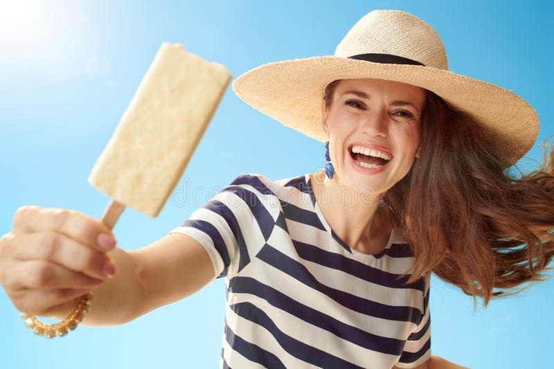 Happy young woman against blue sky giving ice cream on stick royalty free stock photo
