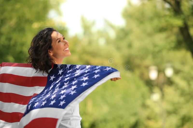 Happy young woman with American flag in park royalty free stock photo