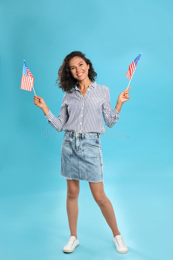 Happy young woman with American flags on background. Happy young woman with American flags on blue background stock images
