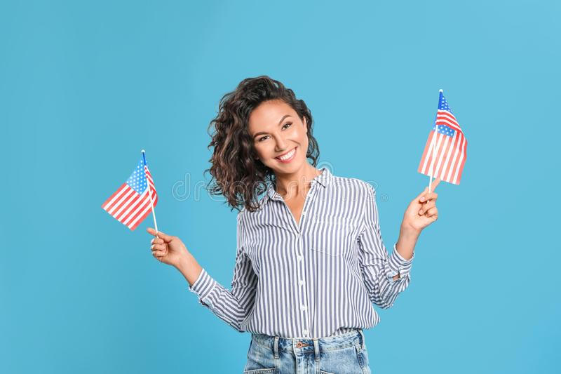 Happy young woman with American flags. On blue background royalty free stock photos
