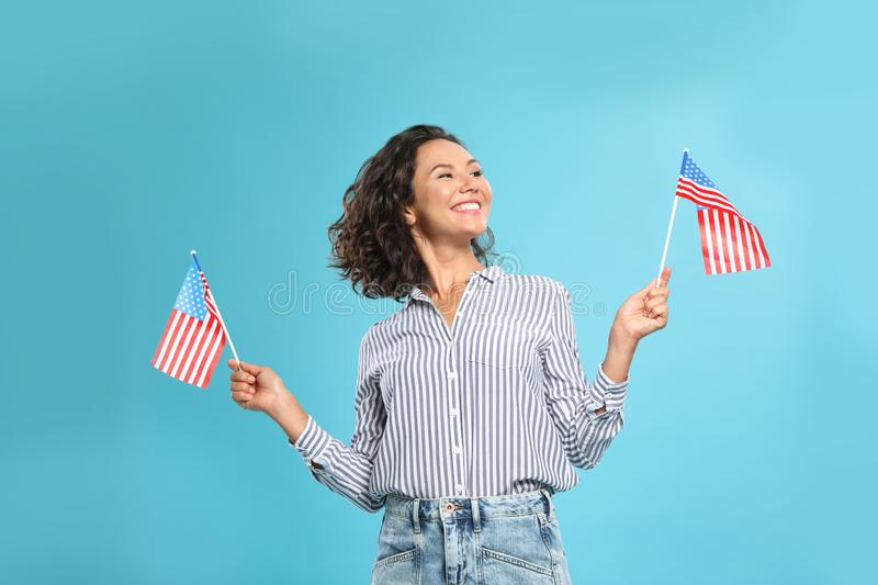 Happy young woman with American flags. On blue background stock photo