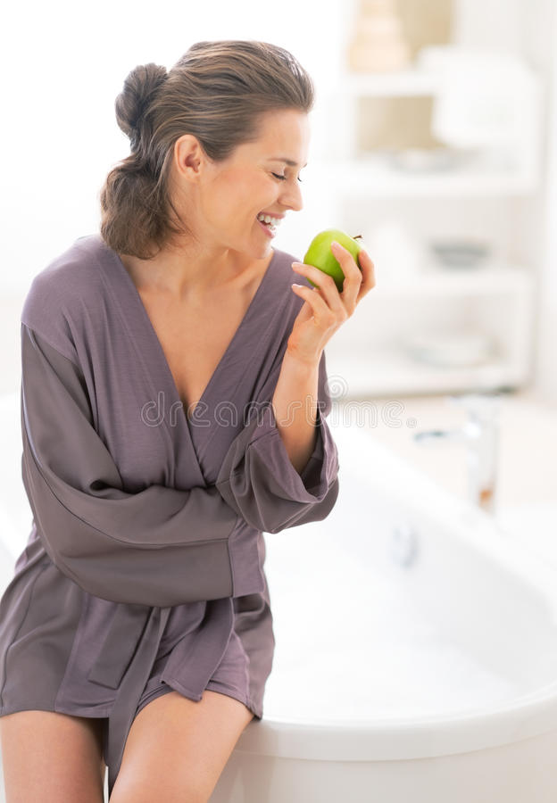 Happy Young Woman With Apple Near Bathtub Stock Photo