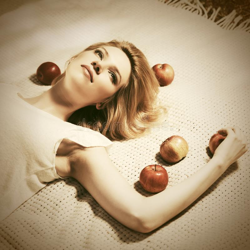 Happy young woman with apples lying on plaid royalty free stock photography