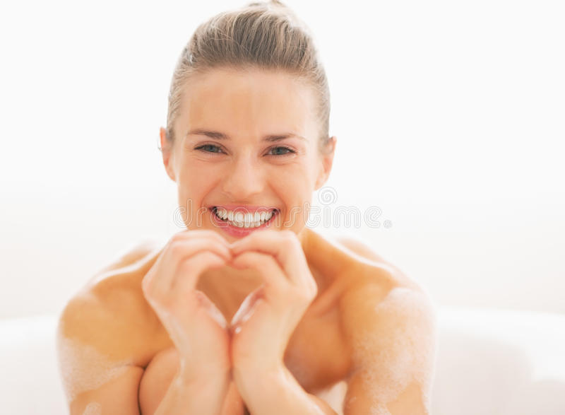 Happy young woman in bathtub showing heart with hands stock photos