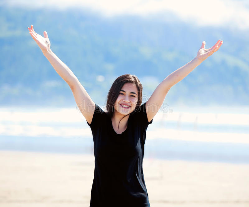 Happy Young Woman On Beach, Arms Outstretched Stock Photo