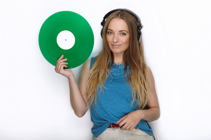 Happy young woman in big black professional dj headphones holding trendy green colorful vinyl record posing against white studio b. Happy young lady in big black stock photos