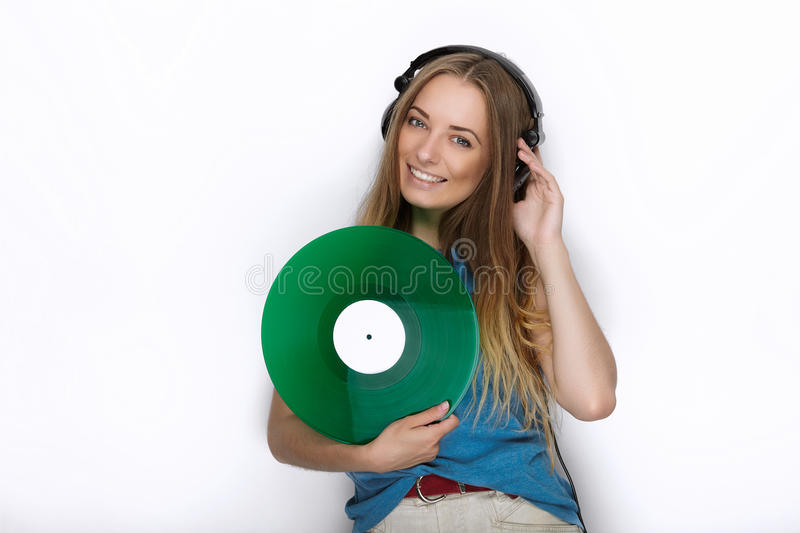 Happy young woman in big black professional dj headphones holding trendy green colorful vinyl record posing against white studio b stock photo