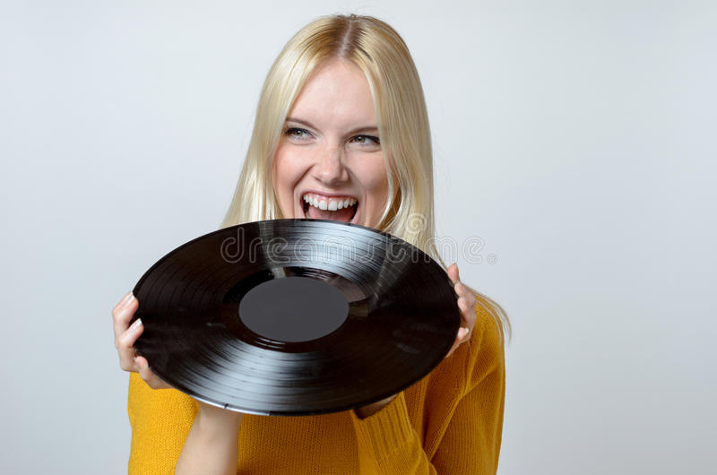 Happy Young Woman biting a Vinyl Record royalty free stock photos