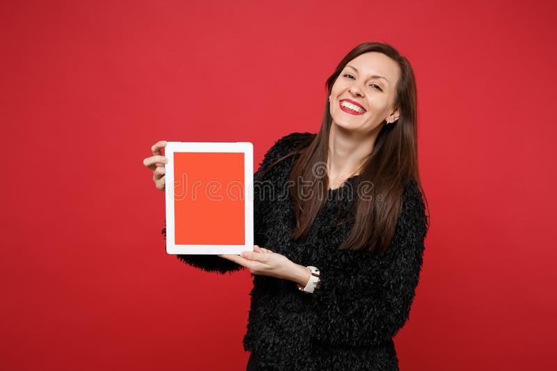 Happy young woman in black fur sweater holding tablet pc computer with blank empty screen isolated on red wall stock photo