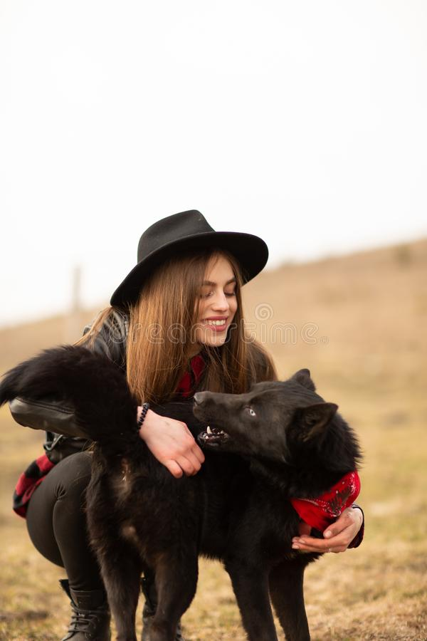 Happy young woman with black hat, plaing with her black dog on the shore of the lake royalty free stock image