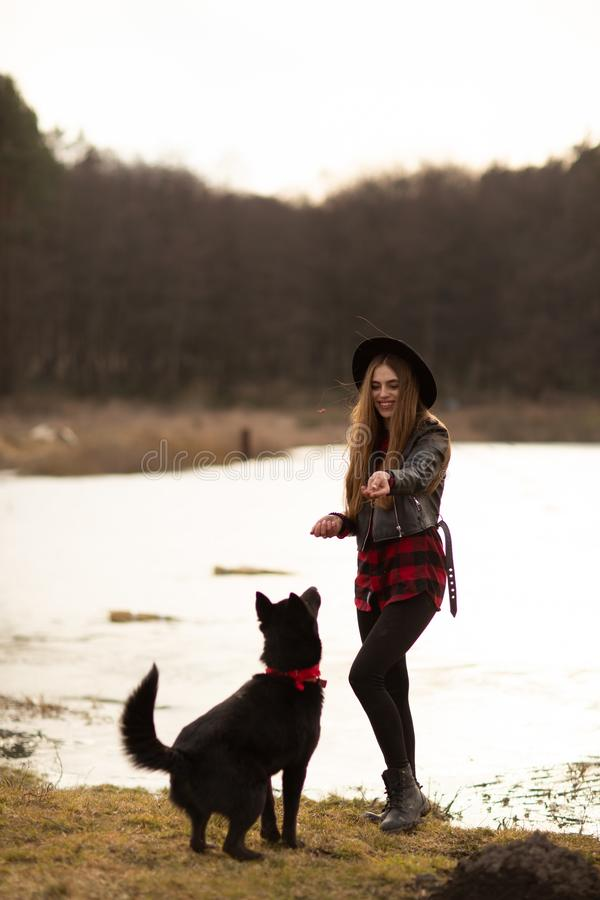 Happy young woman with black hat, plaing with her black dog on the shore of the lake royalty free stock photo