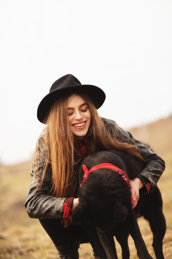 Happy young woman with black hat, plaing with her black dog on the shore of the lake royalty free stock photos
