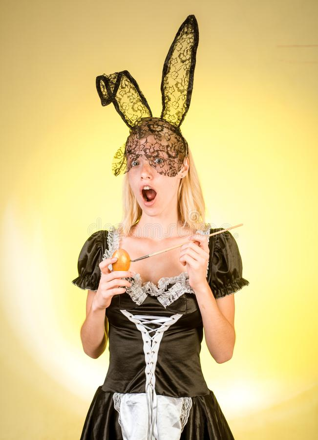 Happy young woman in black mask Easter bunny looks surprised at camera drawing golden paint Easter egg. Funny face royalty free stock photos