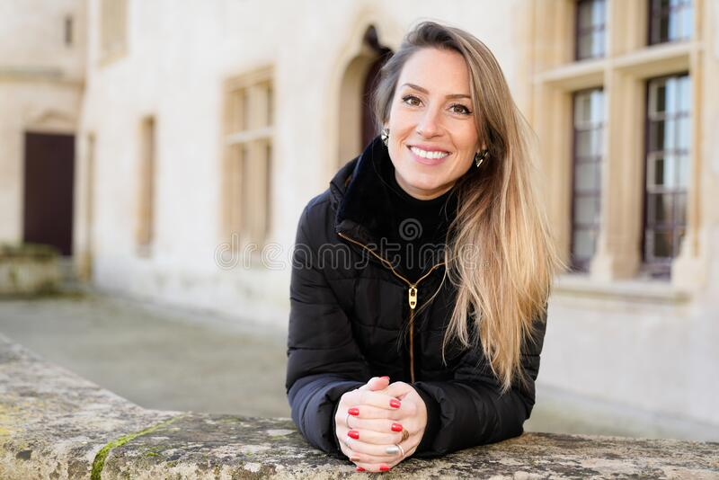 Happy young woman with blonde long hair tourist posing around ancient streets royalty free stock photography