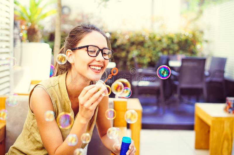 Happy young woman blowing soap bubble in bar restaurant - Beautiful girl having fun outdoor stock image