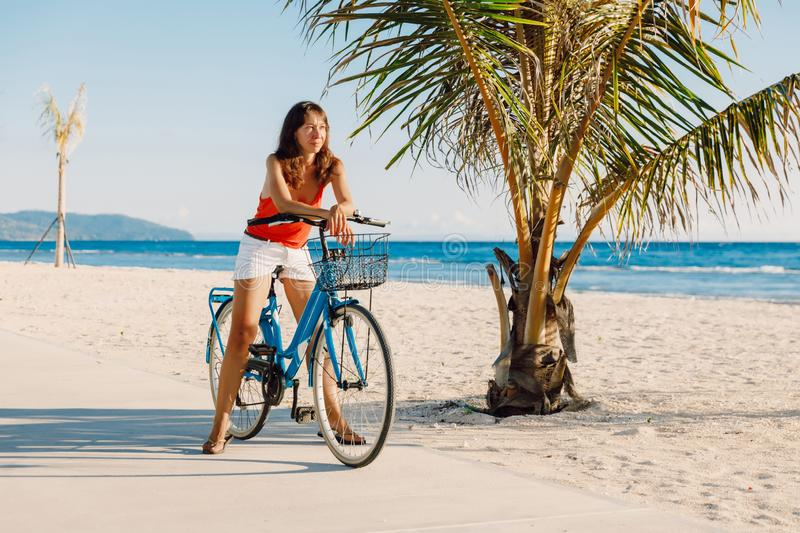 Happy young woman on blue bicycle near ocean in tropical island royalty free stock photos
