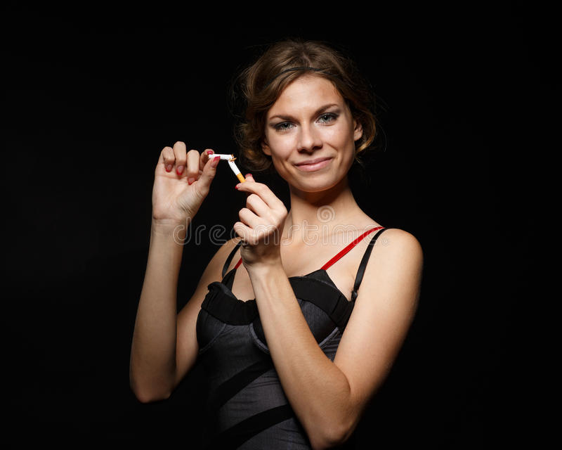 Happy young woman with the broken cigarette. Happy young confident woman, quitting smoking, stands with the broken cigarette on a black background. Concept royalty free stock photos