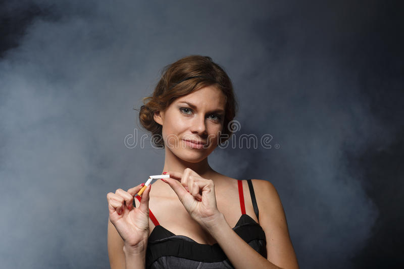 Happy young woman with the broken cigarette. Happy young confident woman, quitting smoking, stands with the broken cigarette on a dark background with smoke royalty free stock photo