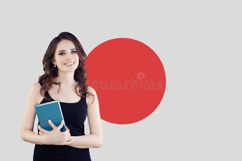 Happy young woman brunette against the Japan flag background royalty free stock photography