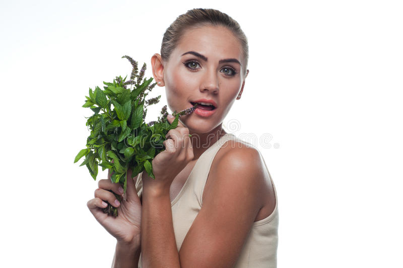 Happy young woman with with a bundle of fresh mint stock photo