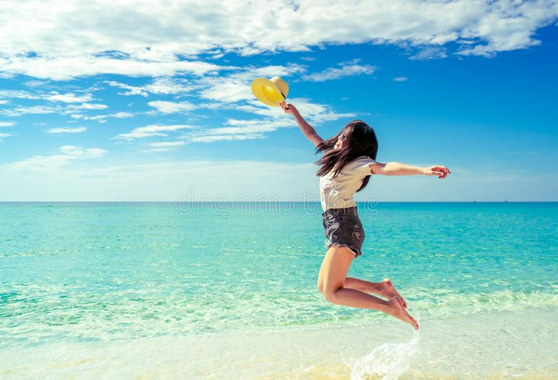 Happy young woman in casual style fashion and straw hat jumping at sand beach. Relaxing, fun, and enjoy holiday at tropical stock photography