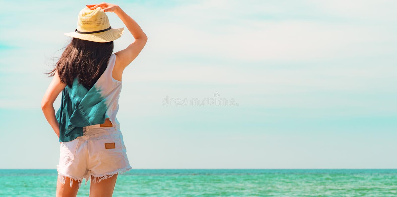 Happy young woman in casual style fashion and straw hat standing at sea beach. Relaxing and enjoy holiday at tropical paradise royalty free stock photos