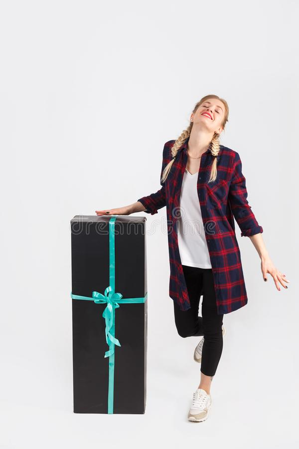 Happy young woman in casual style, standing with big gift box, isolated on a white background royalty free stock photos