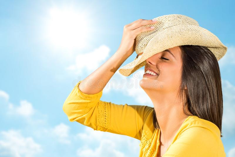 Happy young woman with charming smile against blue sky. stock photo