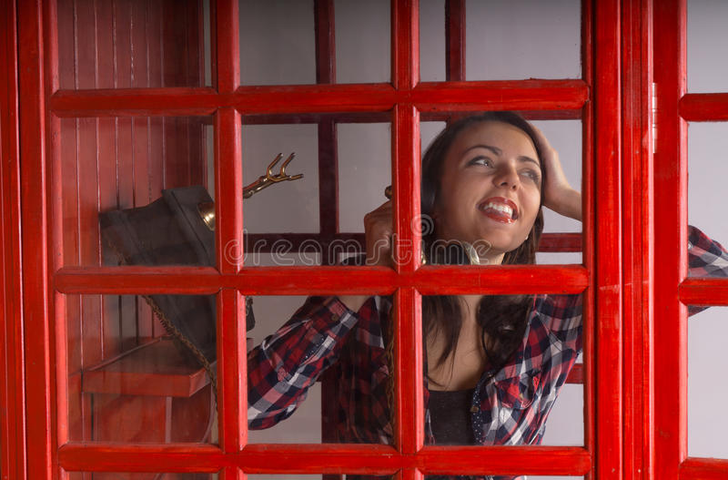 Happy young woman chatting on a public phone royalty free stock photography