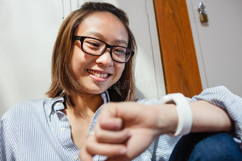 Happy young woman checking time on smartwatch in locker room royalty free stock photography
