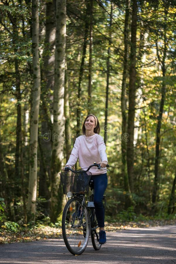 Happy young woman riding a bike royalty free stock images