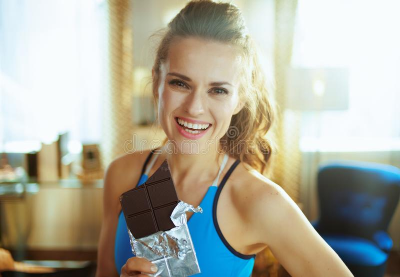 Happy young woman with chocolate bar in modern living room. Portrait of happy young woman in fitness clothes with chocolate bar in the modern living room royalty free stock photo