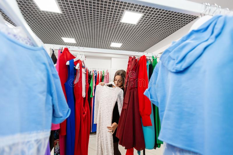 Happy young woman choosing clothes in mall or clothing store. royalty free stock photos