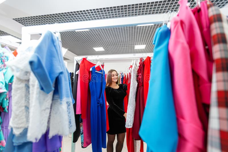 Happy young woman choosing clothes in mall or clothing store. stock photos