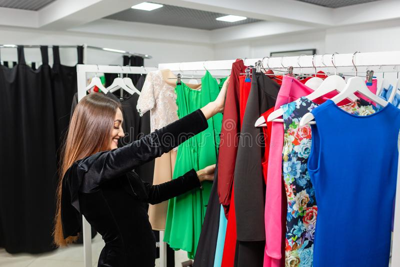 Happy young woman choosing clothes in mall or clothing store. stock photography